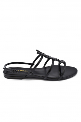 Saint Laurent Cassandra flats sandals in black patent leather with thin straps and YSL logo signature in black metal at the fron